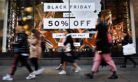 Shoppers walk past Black Friday promotion posters