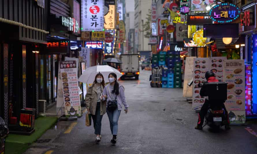 Two women wearing face masks walk beneath an umbrella along an alleyway in Seoul. South Korea reported 34 new cases of coronavirus on Sunday.