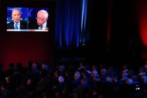 Audience members watch democratic presidential candidates Mike Bloomberg and Bernie Sanders speak on a monitor during the Democratic presidential primary debate in Las Vegas, Nevada.