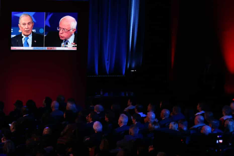 Audience members watch democratic presidential candidates Mike Bloomberg and Bernie Sanders speak on a monitor during the Democratic presidential primary debate in Las Vegas, Nevada.