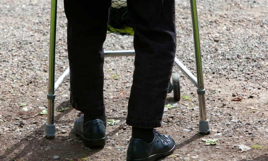 A man takes a step using a walker