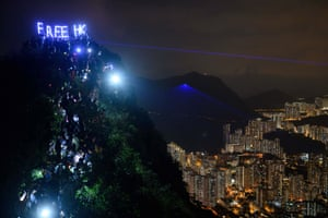"""Pro-democracy activists hold up LED letters reading """"Free HK"""" as others form a human chain on Lion Rock in Hong Kong."""