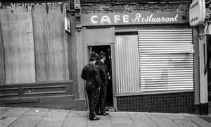 Police move into a boarded-up cafe to check for demonstrators who had been throwing missiles from upper floors