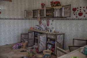 Crockery and pots of artificial flowers still sit in a room