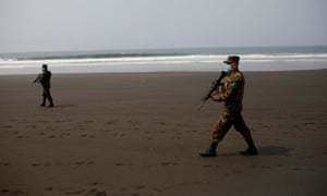 Salvadoran soldiers walk during a patrol at El Majahual beach during a quarantine throughout the country, as the government undertakes steadily stricter measures to prevent the spread of the coronavirus disease