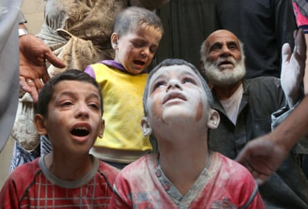 Syrian boys cry following Russian air strikes on the rebel-held Fardous neighbourhood of the northern embattled Syrian city of Aleppo