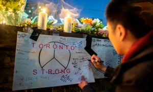 A mourner writes a message during a vigil near the site of the van attack in Toronto, Canada, on 24 April 2018.