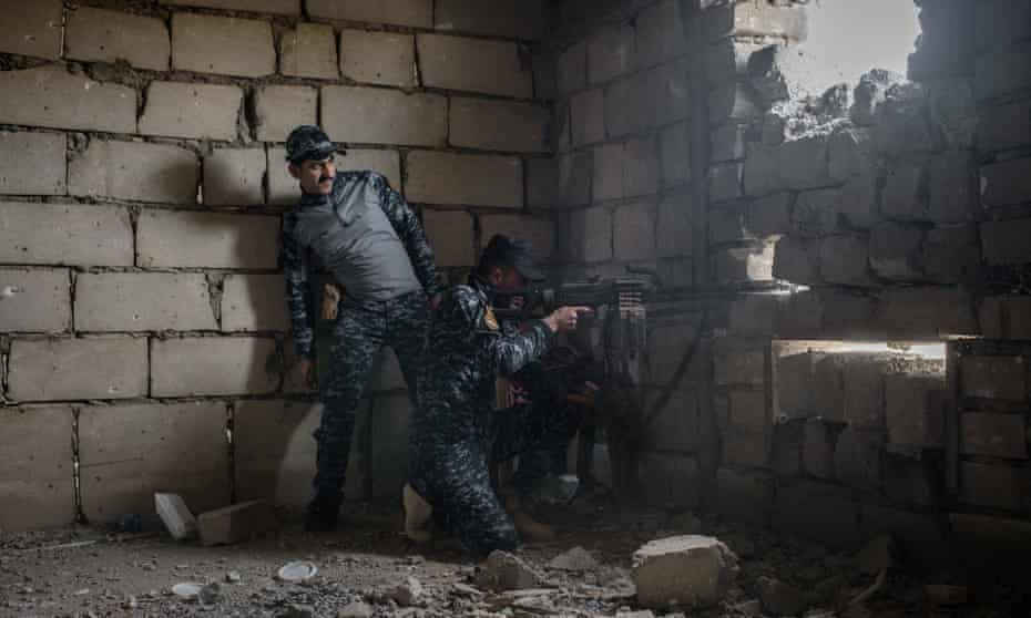 A member of the Iraqi Federal Police fires at Isis positions across the street in west Mosul.