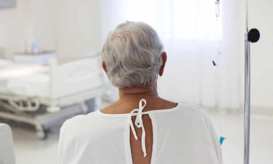 Older patient wearing gown in hospital room