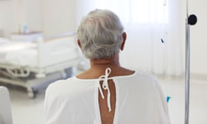back of elderly man in hospital gown