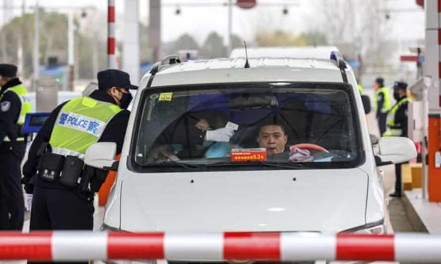A police officer uses a thermometer to take a driver's temperature at a checkpoint in Wuhan.