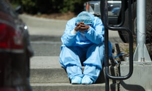 A tired healthcare worker sitting on steps by the Brooklyn Hospital Center in New York