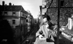 French writer Albert Camus smoking cigarette on balcony outside his publishing firm office.