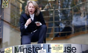 Gail Bradbrook kneels on top of the doorway into the Department for Transport in central London on Tuesday morning.