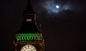 Big Ben and the houses of parliament at night-time, with a bright moon shining above