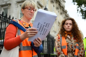 An activist from the Insulate Britain campaign with a letter for Boris Johnson outside Downing Street today. The group, which wants the government to properly insulate all homes in Britain, is suspending its road-blocking protests until 25 October.