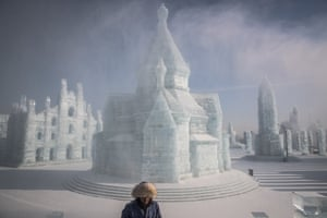 A worker walks next to ice sculptures during the annual Harbin international ice and snow festival.