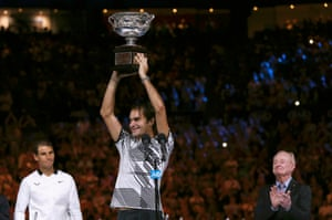 Federer lifts the Norman Brookes Challenge Cup high as Nadal and tennis legend Rod Laver look on.