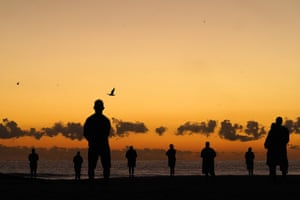 People commemorate Anzac Day at dawn on Currumbin beach on the Gold Coast.