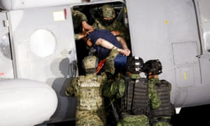 Soldiers escort drug lord El Chapo into a helicopter in Mexico City.