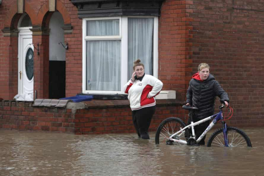 boy pushing a bicycle across a flooded street in Bentley, with girl on mobile looking on