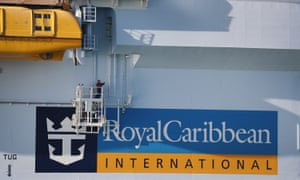 A worker paints the side of the Royal Caribbean Symphony of the Seas Cruise ship
