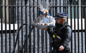 A police officer in Downing Street carries a gift basket for Boris Johnson and his partner Carrie Symonds sent to mark the birth of their son