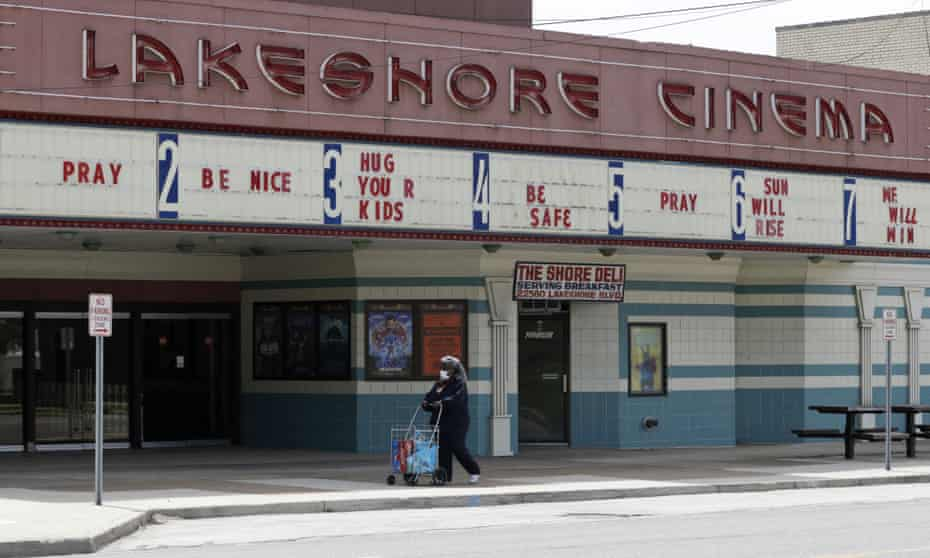 A woman wearing a mask walks with her groceries past a closed Lakeshore Cinema theatre in Euclid, Ohio.