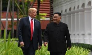 Kim Jong-un walks with Donald Trump during a break in talks.