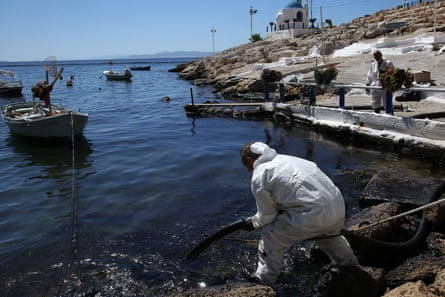 Workers struggle to remove an oil spill from a beach in the coastal zone of Athens, Greece