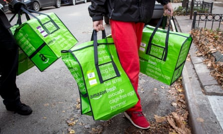 Amazon workers deliver groceries in New York. The delivery bags could soon be a familiar sight in Britain.
