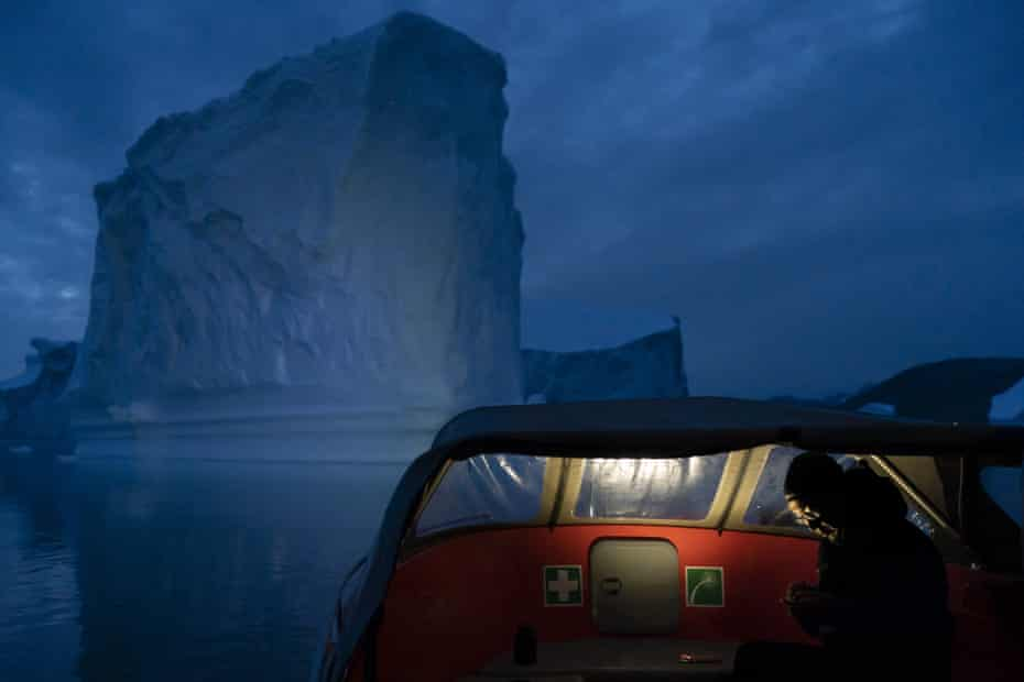A boat navigates at night near a large iceberg in eastern Greenland, August