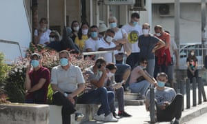 Patients wait in line in front of the Uzice General hospital in Uzice, Serbia, on Monday.
