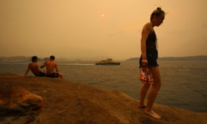 Beachgoers stand on a cliff as smoke haze from bushfires blankets the Sydney CBD, 21 December 2019