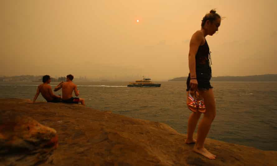 Beachgoers stand on a cliff as smoke haze from bushfires blankets the Sydney CBD, 21 December 2019