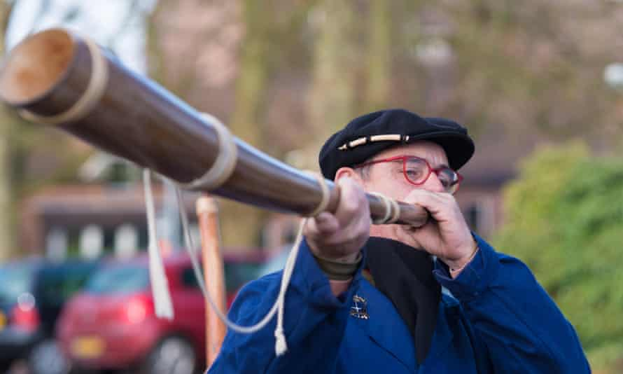 Unknown man blowing a so called midwinterhorn, a traditional handmade wooden instument. It is used in the Netherlands.
