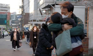 A parent embraces their child before taking the annual college entrance exam amid the coronavirus pandemic in front of an exam venue in Seoul, South Korea, on December 3, 2020.