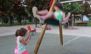 One child plays on swing while another plays with Hybrid Play app on a smartphone.