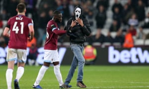 One of the West Ham pitch invaders was wearing a Scream mask and is ushered away by Arthur Masuaku.