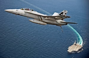 Atlantic Ocean An F/A-18F Super Hornet jet flies over the USS Gerald R. Ford as the U.S. Navy aircraft carrier tests its EMALS magnetic launching system, which replaces the steam catapult, and new AAG arrested landing system