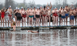 Christmas Day swimmers at the Serpentine in Hyde Park, London experience goosebumps before their cold water dip.
