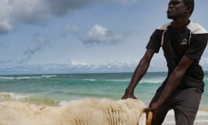 A man leads his sheep to the sea for a wash near Guédiawaye, Dakar.
