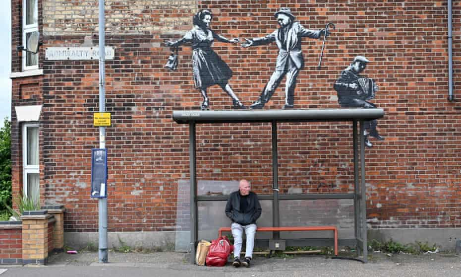 A man waits at a bus stop below a graffiti artwork of a couple dancing to an accordion player, by street artist Banksy, on a wall in Great Yarmouth