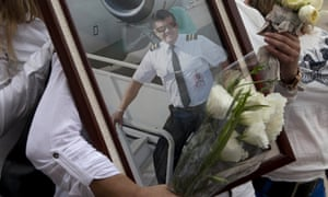 A relative holds a portrait of Marcelo Quiroga, pilot of the La Mia plane that crashed in Colombia, apparently due to lack of fuel.