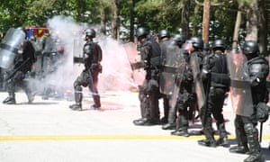 Officers in riot gear dodge an exploding firework at Stone Mountain Park.