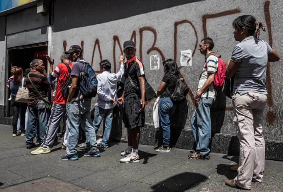 People queue to withdraw money from a cash machine in Venezuela