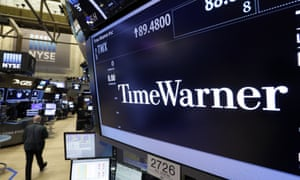 A trader walks by the post that handles Time Warner on the floor of the New York Stock Exchange on Monday.