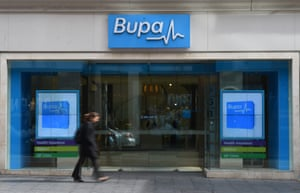 A woman walks past a Bupa Health Insurance branch in Sydney.