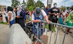 A woman in a wheelchair leans on a street barricade as people outside the memorial for George Floyd are asked to stand for nine minutes in memory of his death.