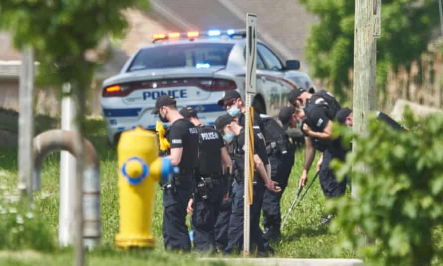 Police officers look for evidence at the scene of the crash in London, Ontario, on 7 June.